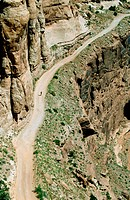 Cyclist bicycling up the Shafer Trail, Island in the Sky, Canyonlands National Park. Utah, USA