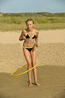 Hula hoop on the beach - Young girl playing with a hoop on the sand beach