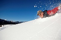Boy sliding down snow slope