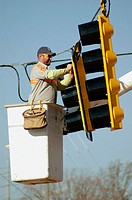 Electrician working on new turn signals on highway for better traffic flow, on goose neck hoist in the air.