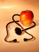 Conceptual photograph of the saying, ´An apple a day keeps the doctor away,´ showing a stethoscope and an apple.
