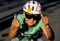 Active and vivacious 80 year old female bicyclist wearing a safety helmet.