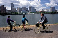 Bicycle commuters riding along the Willamette River in Portland, Oregon.