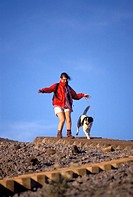 Woman jogging with her dog down a stepped hillside.