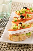 Canapes of turkey, brie, tomatoe and avocado