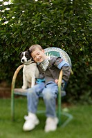 Boy, age five, and Jack Russell Terrier dog sit on decorative chair