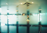 People in conference room, seen through semi-opaque glass wall