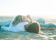 Teenage couple lying on beach