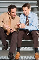 Colleagues comparing mobile phones