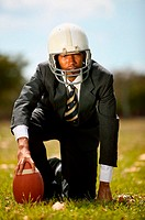 Businessman playing american football