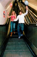 Couple with balloons on escalator