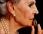 Senior woman applying lipstick