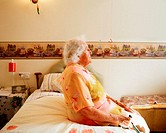 Elderly woman sitting on her bed