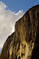 Blue sky, clouds, and sunlight on sheer granite cliff face wall of El Capitan, Yosemite Valley, Yosemite National Park, California
