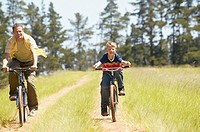 Father and son riding bikes in a field