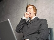 Businessman yawning while using his laptop