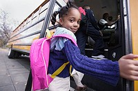 Portrait of girl getting on school bus