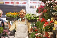 African American woman holding plants in nursery