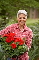 Mature woman holding flowering plant