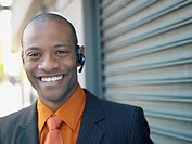 Smiling businessman using hands free cell phone