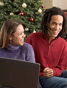 Couple with laptop in front of Christmas tree