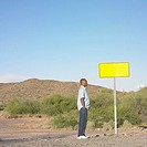 Side view of man standing by road sign