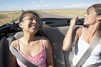 Two women laughing in convertible