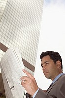 Businessman reading financial newspaper (thumbnail)