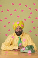 Portrait of businessman wearing turban with sticky notes attached everywhere