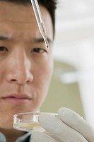 Close up of man with eye dropper and petri dish