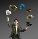 Young businessman juggling six hats