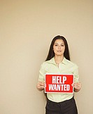Businesswoman holding a help wanted sign