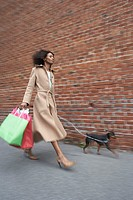 Woman with shopping bags walking dog