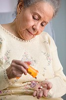 Elderly woman shaking out pills