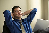 Businessman smiling and relaxing at desk