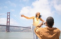 Man photographing woman in front of Golden Gate Bridge