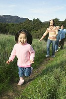 Young girl running ahead of family