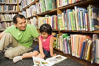 Father and daughter reading books in library