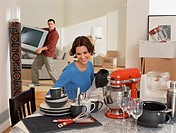 Young woman admiring kitchenware while partner moves tv