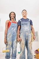 Portrait of couple in overalls painting