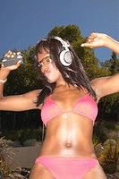 Woman in bikini dancing while listening to music with headphones