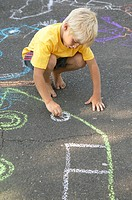 Young boy drawing in chalk on the pavement