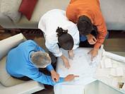 A couple discusses blueprints with an architect