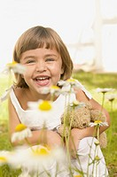Young girl crouching behind daisies in a garden