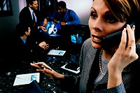 Businesswoman talking on a mobile phone with three businessmen talking behind her