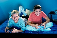 Teenage boy and a teenage girl playing video games