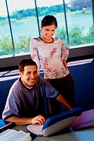 Portrait of young man in front of a laptop with a teenage girl behind him