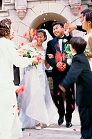 Flower petals being thrown on a bride and groom