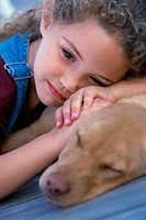 Close-up of a young girl lying with her dog