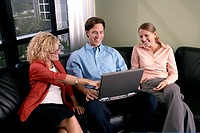 Businessman using a laptop with two businesswomen sitting beside him